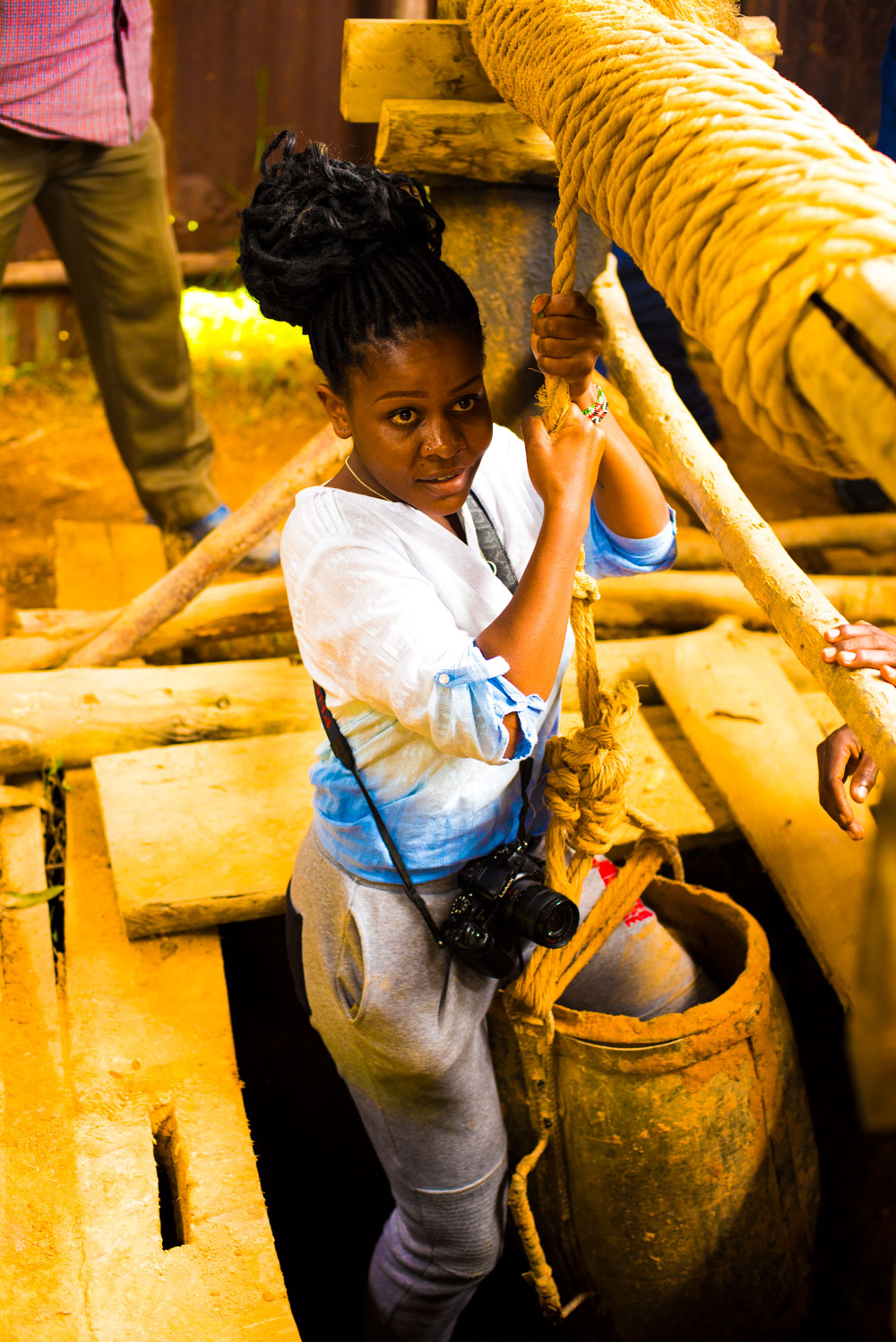 Young lady holds rope while entering a gold mine in Western Kenya